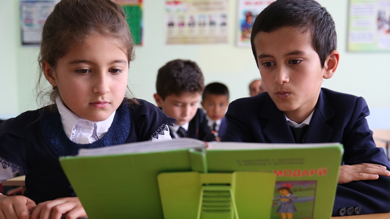 Credit/ALT text: Two students read from a book in the #39 school in Tajikistan. Credit: GPE/Carine Durand