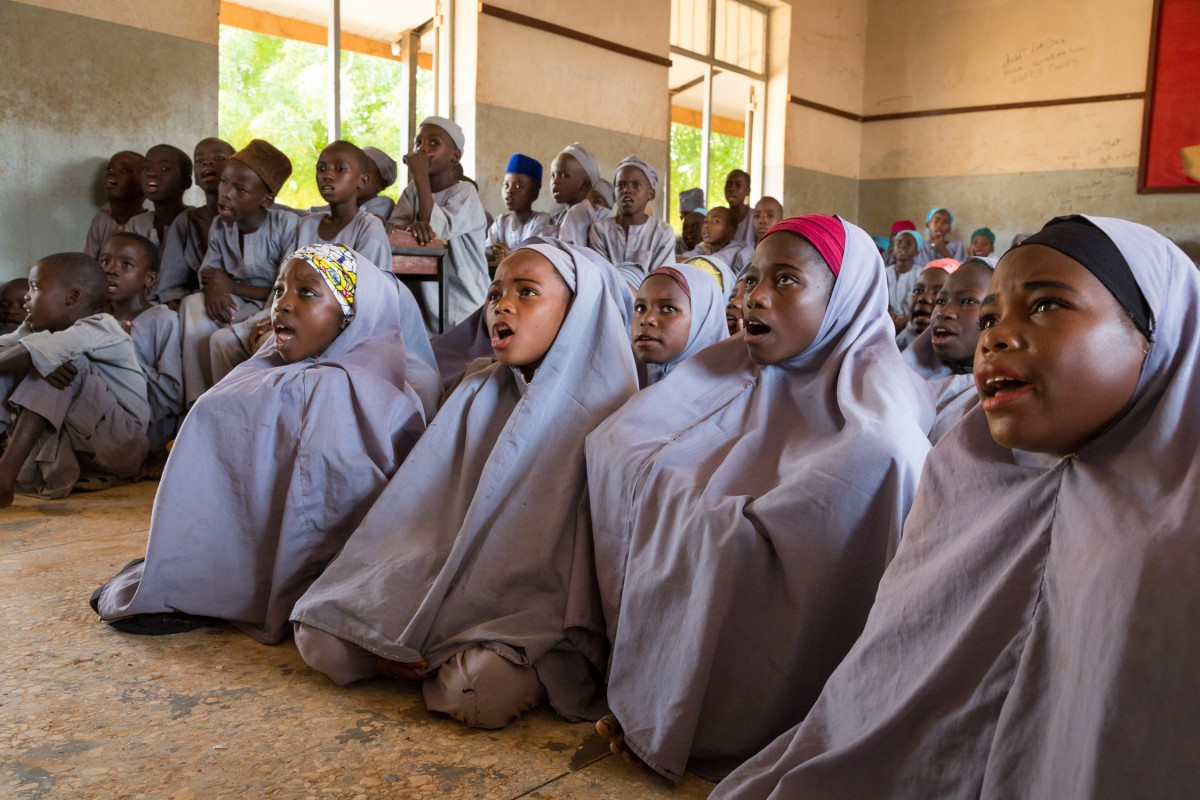 Sumayya Ado, in red headscarf, sits on the floor with her female peers in a classroom at Janbulo Islamiyya Primary School. Nigeria Credit: GPE/Kelley Lynch