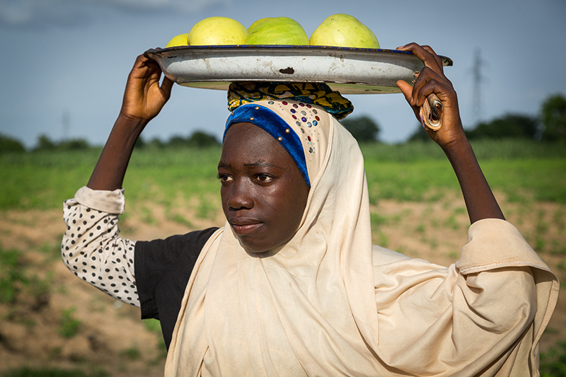 Rashida Ali, 14, stands with a tray of melons on her head. Nigeria Credit: GPE/Kelley Lynch