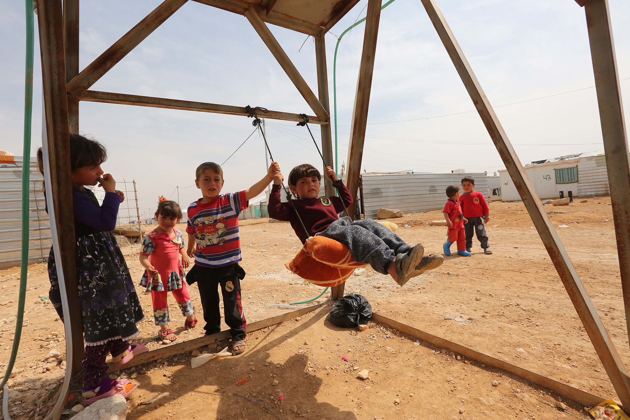 Children playing on a makeshift swing set on a rocky clearing of land inside of a refugee camp.
