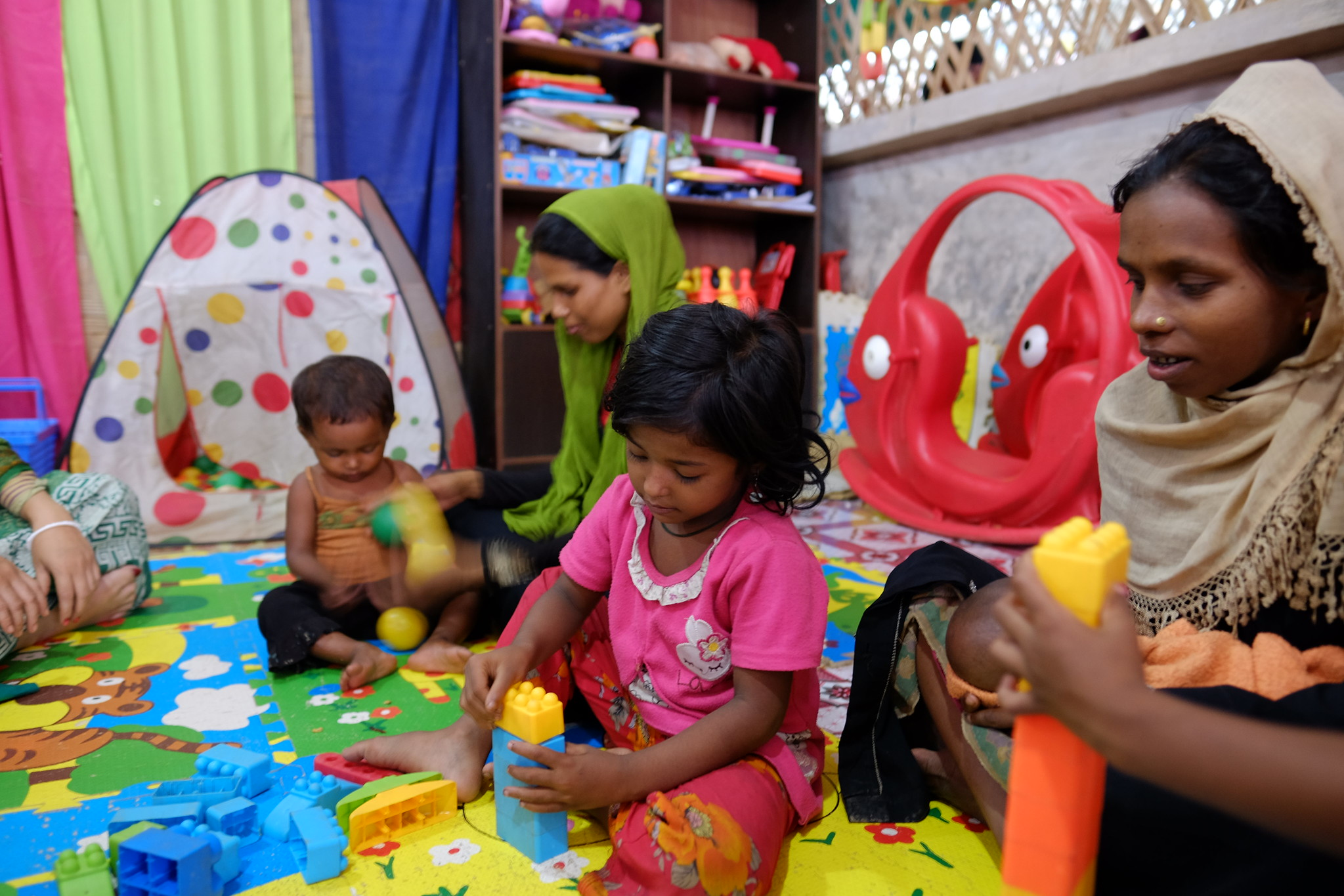 Toddlers and infants in an art therapy space for refugee children with daycare workers watching closely behind them.
