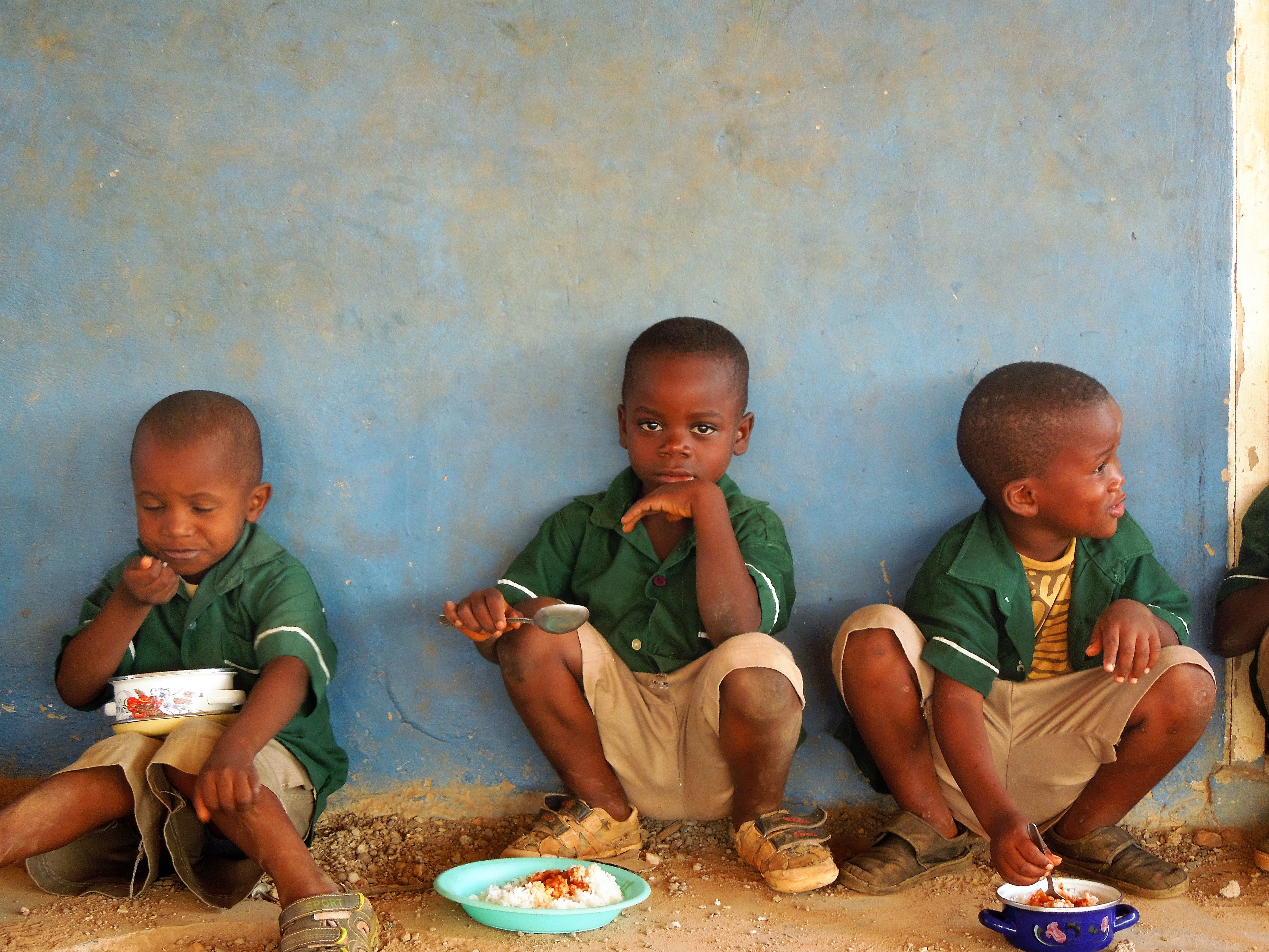 Three boys eating their lunch at school in Fetentaa refugee camp