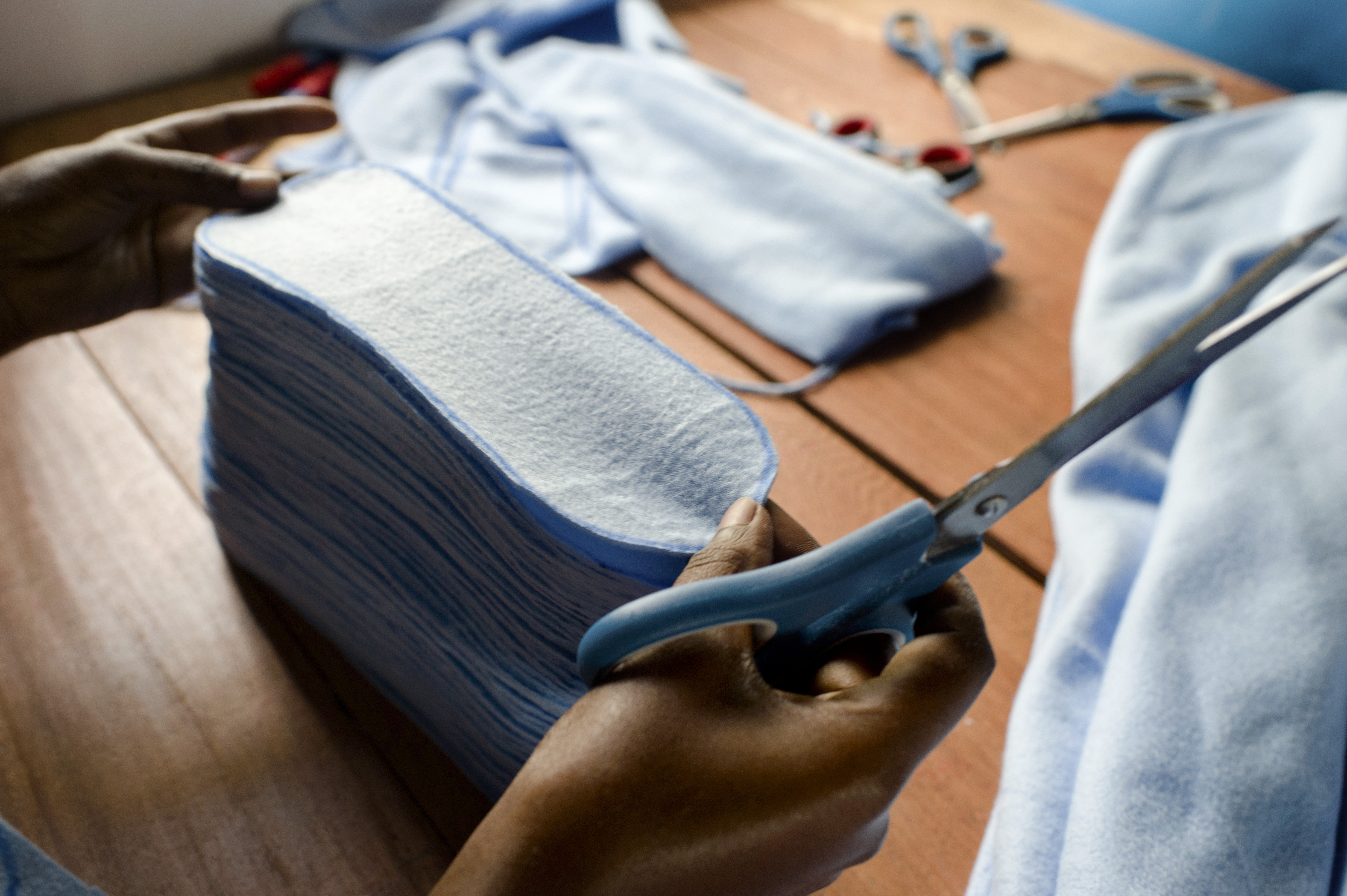A worker trims and stacks sanitary pads before they are lined and sewn at the AFRIpads factory. Started by volunteers in 2009, AFRIpads manufactures reusable fibre sanitary pads. Uganda, Kitengeesa.