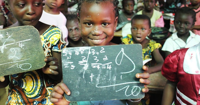 In the Central African Republic, a student is proudly showing her test score in a math class. Her school was closed for a long time due to insecurity in the district but most students came back with GPE supported activities.  Credit: UNICEF/Kim