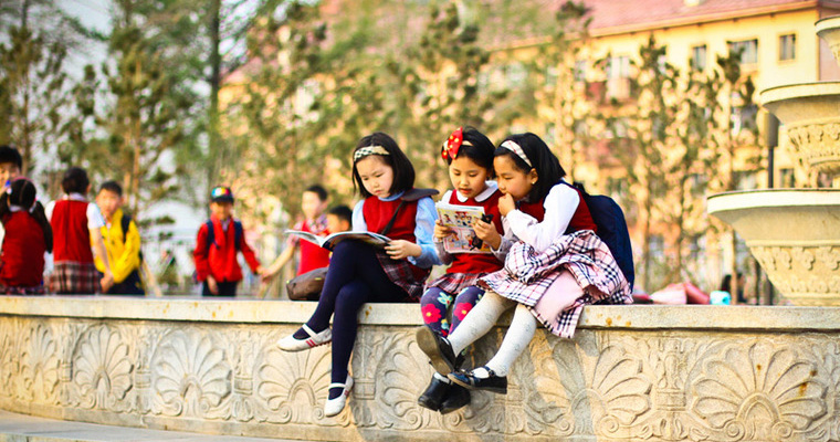 These girls share a book outside after school. This is important because what they are reading helps them gather information that they may need in the future. Credit: GPE/ Enkhtulga Enkhbayar