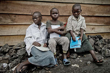 Sukuru is longing to go back to school, which has been closed since the fighting began in mid-November. Here he is earlier this year flanked by two of his schoolmates in Mugunga III camp, DRC. Photo credit: UNHCR/Frederic Noy