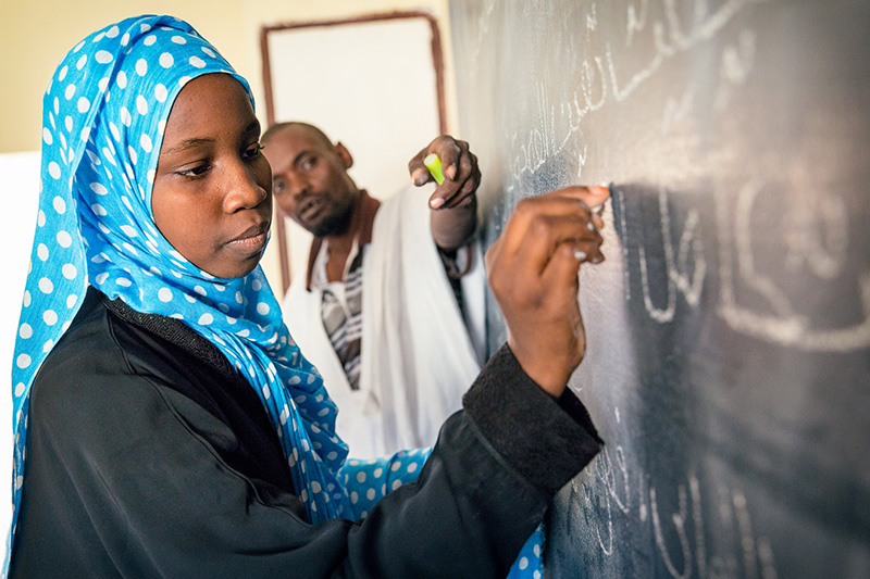 Aichetou Mint Mohamed Ali, 14, in class with teacher and Headmaster Ballaaf Ould Salem Vall. Credit GPE/Kelley Lynch