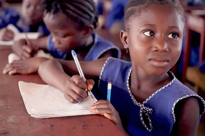 A young girl listens writing in her notebook in class. Credit: GPE/Stephan Bachenheimer