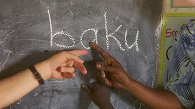 Children point to the word Baku on their classroom chalkboard