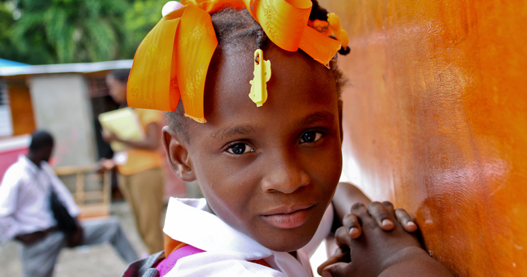 Valentina Metelus, 8, waits outside of her school in the Carrefour neighborhood outside of Port-au-Prince, Haiti. Credit: Save the Children