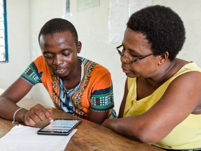 Sixth grade teacher Evelyne Saru Mchori works with ICT Technician James Mwamta who helps teachers enter their TPAD (Teacher Performance Appraisal and Development tool) self-appraisals online. Location: Miritini Primary School, Mombasa County, Kenya. CREDIT: GPE/Kelley Lynch