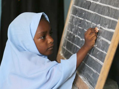 A student writes numbers on the blackboard at the Mnyimbi TuTu Center, North Province, Zanzibar. CREDIT: GPE/Chantal Rigaud