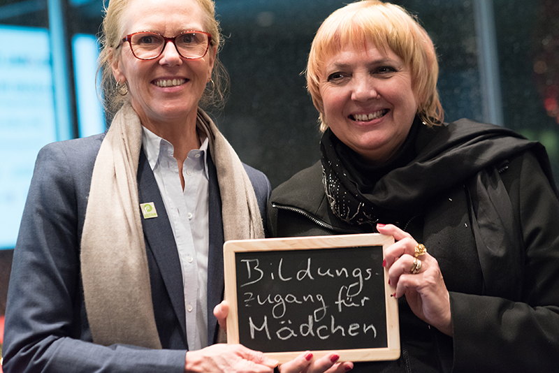 Marion Lieser and Claudia Roth hold a sign that says Access to education for girls Credit: Jonas Walzberg for Global Citizen