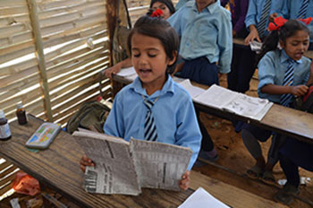 A student reads aloud from her notebook at the Shree Mahendrodaya Higher Secondary School. Sindhupalchowk, Nepal