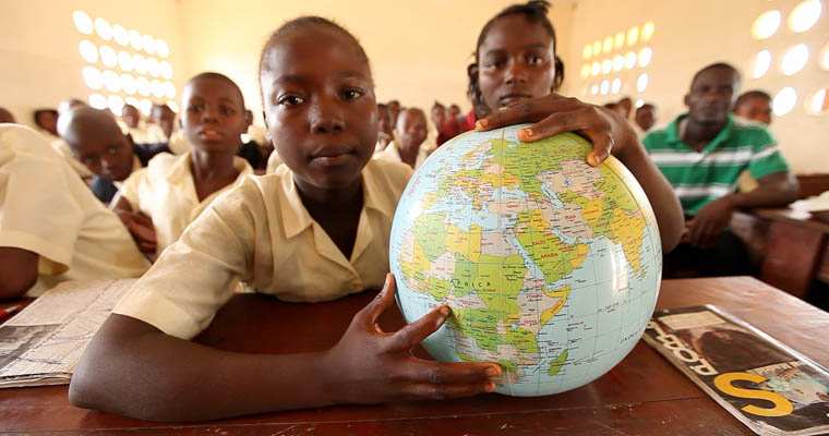 A child at school in Sierra Leone, with a globe showing Africa. Credit: GPE/Stephan Bachenheimer