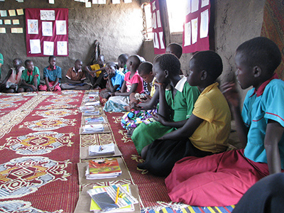 Students sit around the room on a rug with their books in front of them. Gudele West BRAC Community Girls' School, outside Juba. South Sudan. May 2013.