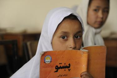 A girl hides behind her book at Ayno Meena Number Two school in the city of Kandahar, Afghanistan. Credit: GPE/Jawad Jalali