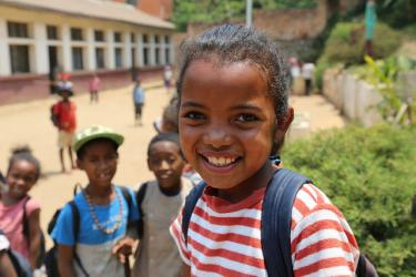 A school girl smiles at the camera in Madagascar. Credit: GPE/Carine Durand