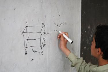 A student solving a problem on the board in the Kandahari High School. Credit: GPE/Jawad Jalali