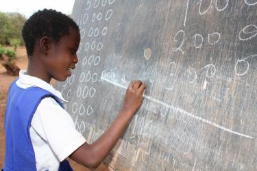 A boy writing at the blackboard in his classroom in DRC. Credit: GPE