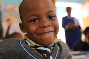 A school children smiles at the camera. Avondale Infant School, Zimbabwe. Credit: GPE/ Carine Durand
