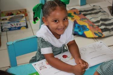 A young girl with a book at the Precious Gems Nursery. Guyana. Credit: GPE/Carolina Valenzuela