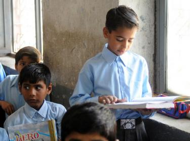 Umair, reads from a book in the classroom. Pakistan. Credit:
