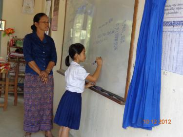 Girl solves a math problem on the board during class while her teacher stands behind her for support, in Phnom Penh, Cambodia. GPE/Deepa Srikantaiah, 2012