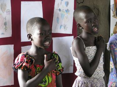 Two girls sing the national anthem of South Sudan at the Gudele West Basic School near Juba. South Sudan. May 2013.  Credit: GPE/David K. Bridges
