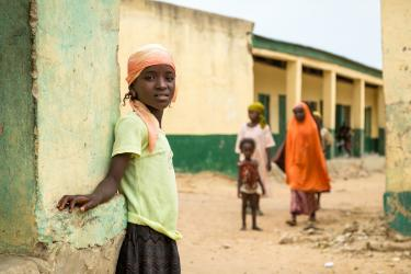 Young girl in front of a primary school, Nigeria. Credit: GPE/Kelley Lynch
