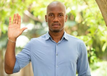 Didier Drogba raises his hand to support GPE's financing campaign.