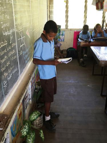 A student reads in front of the class. Port Moresby, Papua New Guinea. Credit GPE/Jeff Ramin
