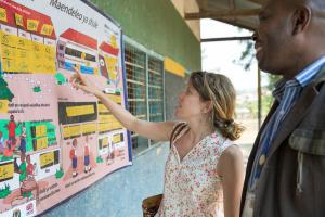 Arianna Zanolini (DFiD) and Laurent Luchagula (Equip-Tanzania) look at a display of school data at Kasimba Primary School, Mpanda District, Katavi Region, Tanzania. Credit: GPE/Kelley Lynch