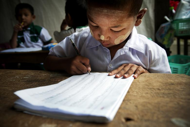 A child practices his writing during a kindergarten class in Tachilek, Myanmar. Credit: UN Photo/Kibae Park