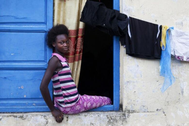 A girl sitting on a window in Republic of Congo. Credit: Sylvain Liechti