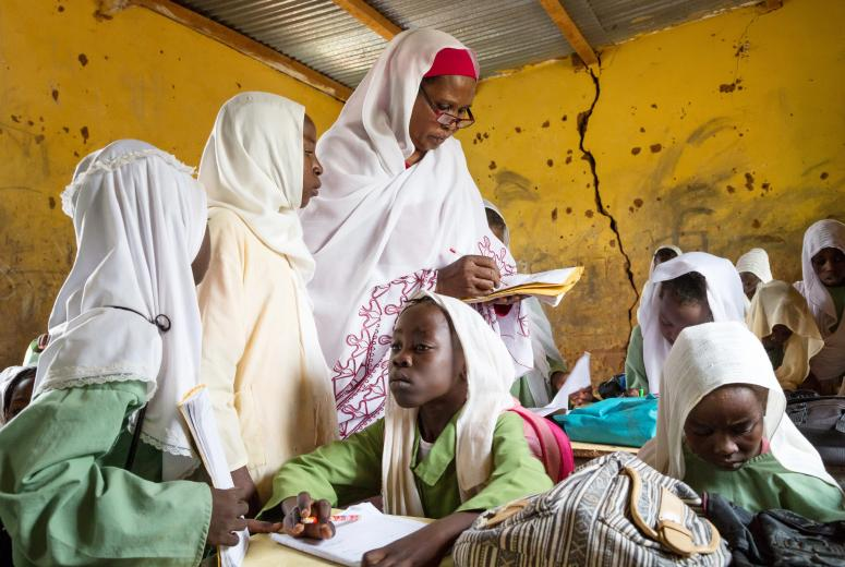 Teacher Duria Balla looks over and corrects student's work; Class 3, Asfia Badr Basic School for Girls, Nile East Locality, Alfayhaa Administrative Unit, Al-Baraka District, near Khartoum, Sudan.