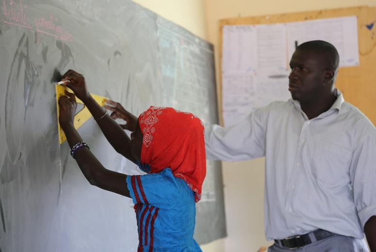 A student draws a rectangle on the blackboard while her teacher looks on. Maka Dieng Primary School in Tivaouane, Senegal. Credit: GPE/Chantal Rigaud
