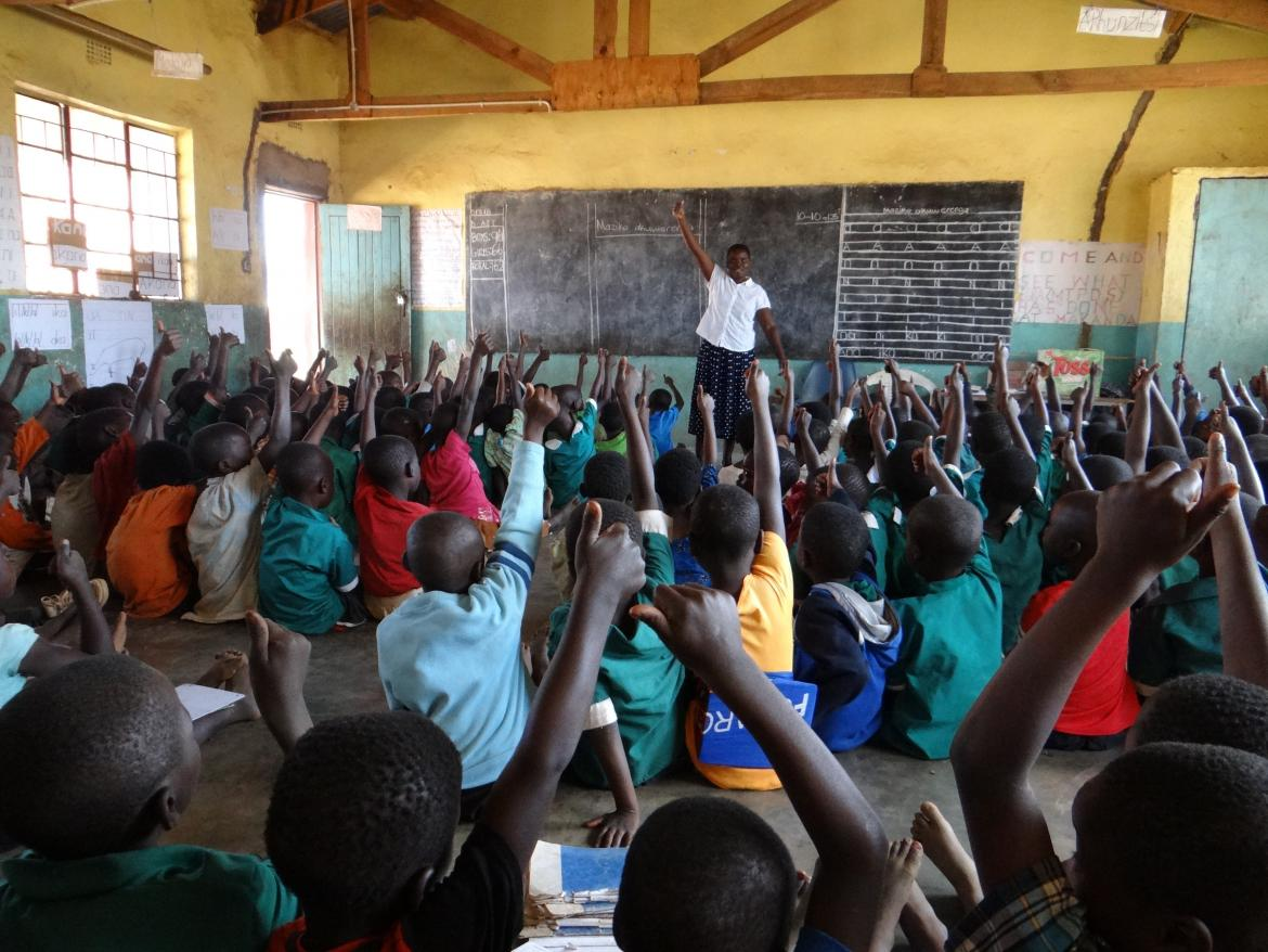 Children and teacher raise their hands. Malawi Primary School. Credit: GPE/Tara O'Connell