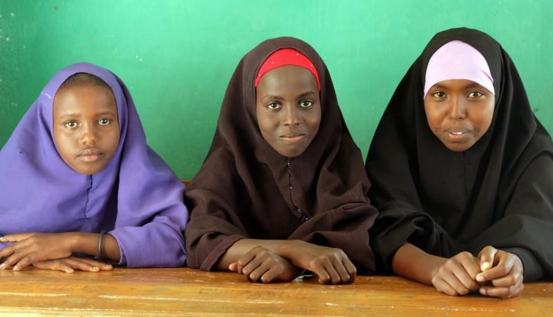3 girls sitting at a desk in their classroom in Somaliland, Somalia. Credit: UNICEF/Hana Yoshimoto