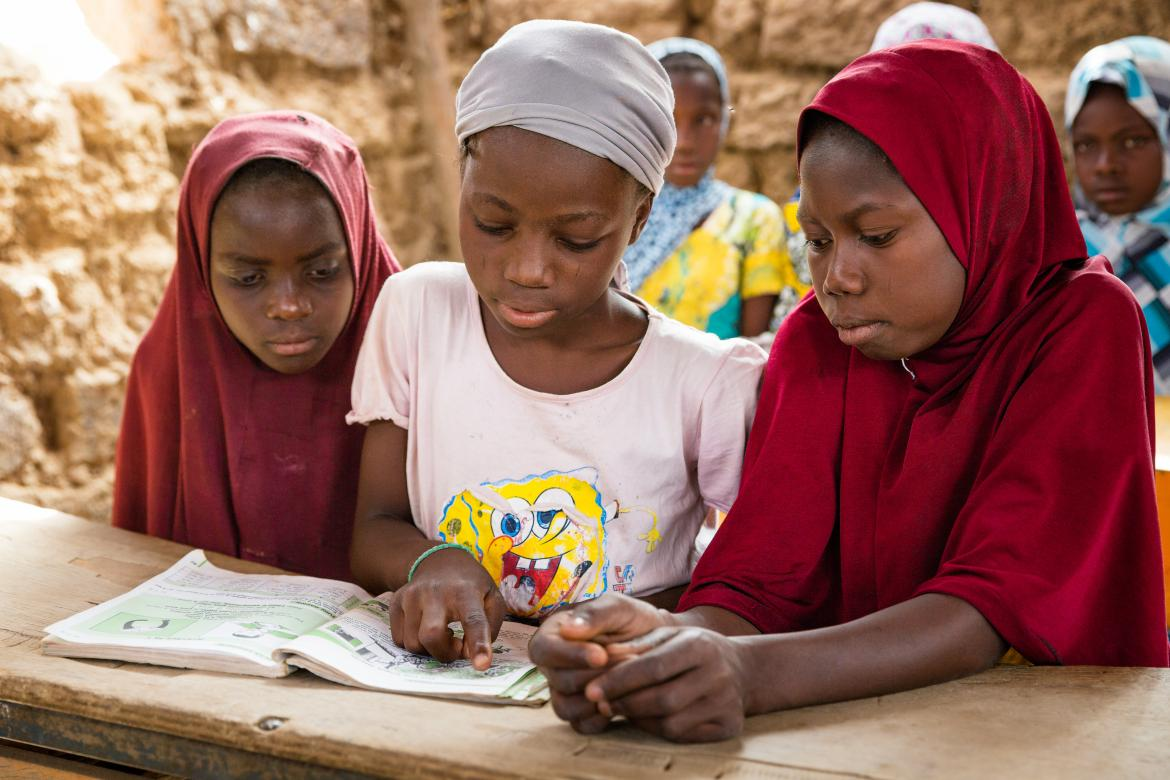 Three students in Niger share a textbook during class. Credit: GPE/Kelley Lynch