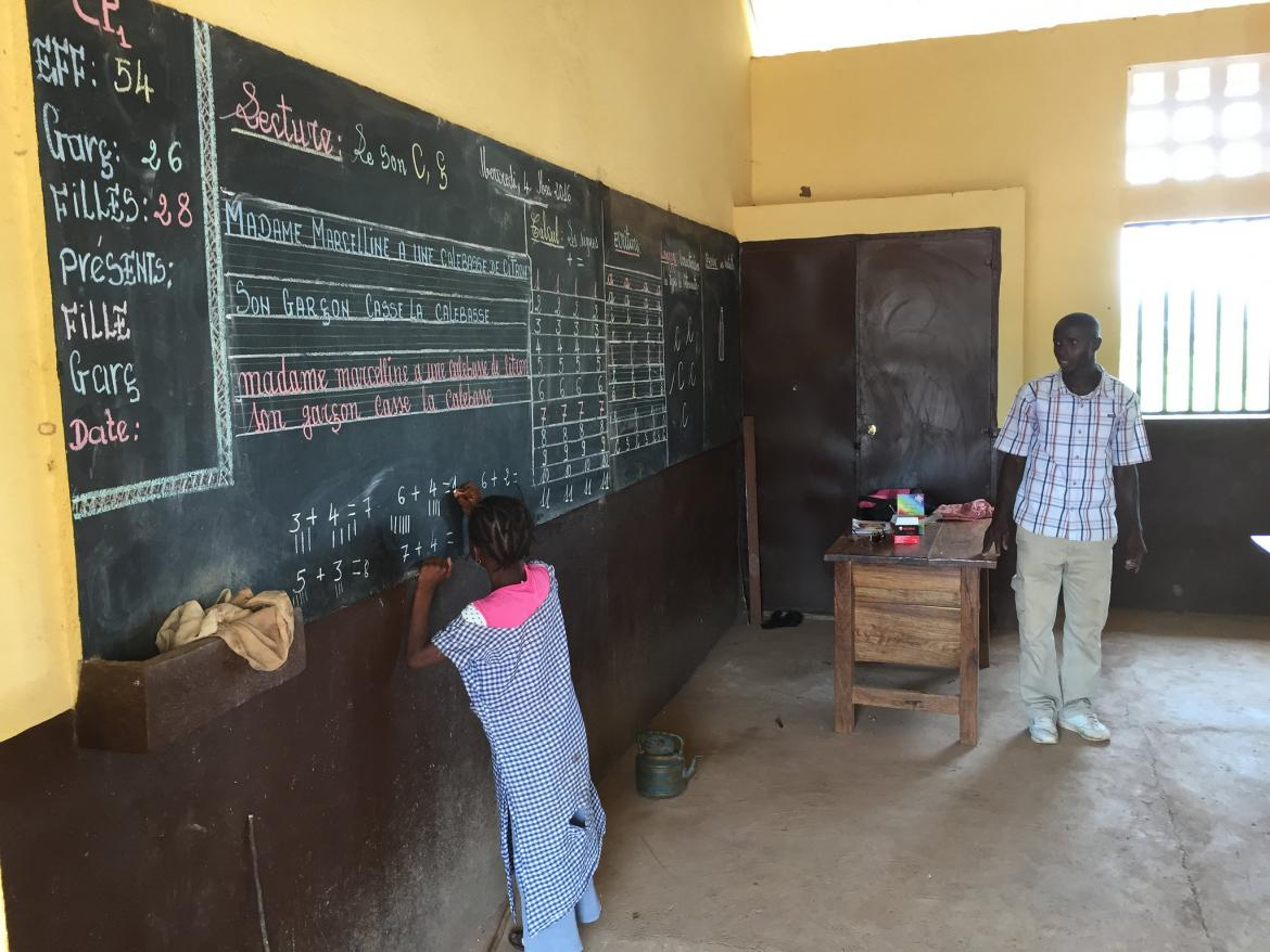 A girl solves a math problem on the blackboard. Alphabaria school, Dabola Area, Guinea