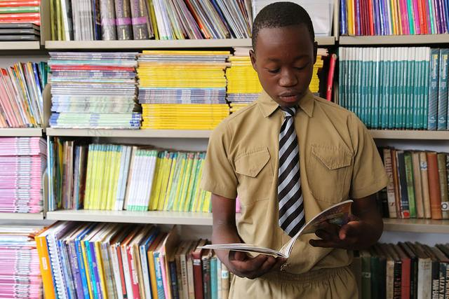 6th grade student Innocent, 13, reads a book in the library at school, Zimbabwe. Credit: GPE/ Carine Durand