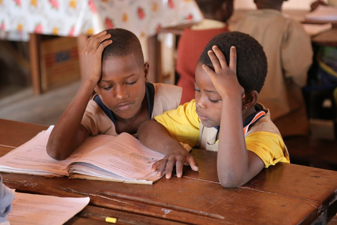 Reading together during a French lesson in a 5th grade classroom at Saka Primary School in Kandi
