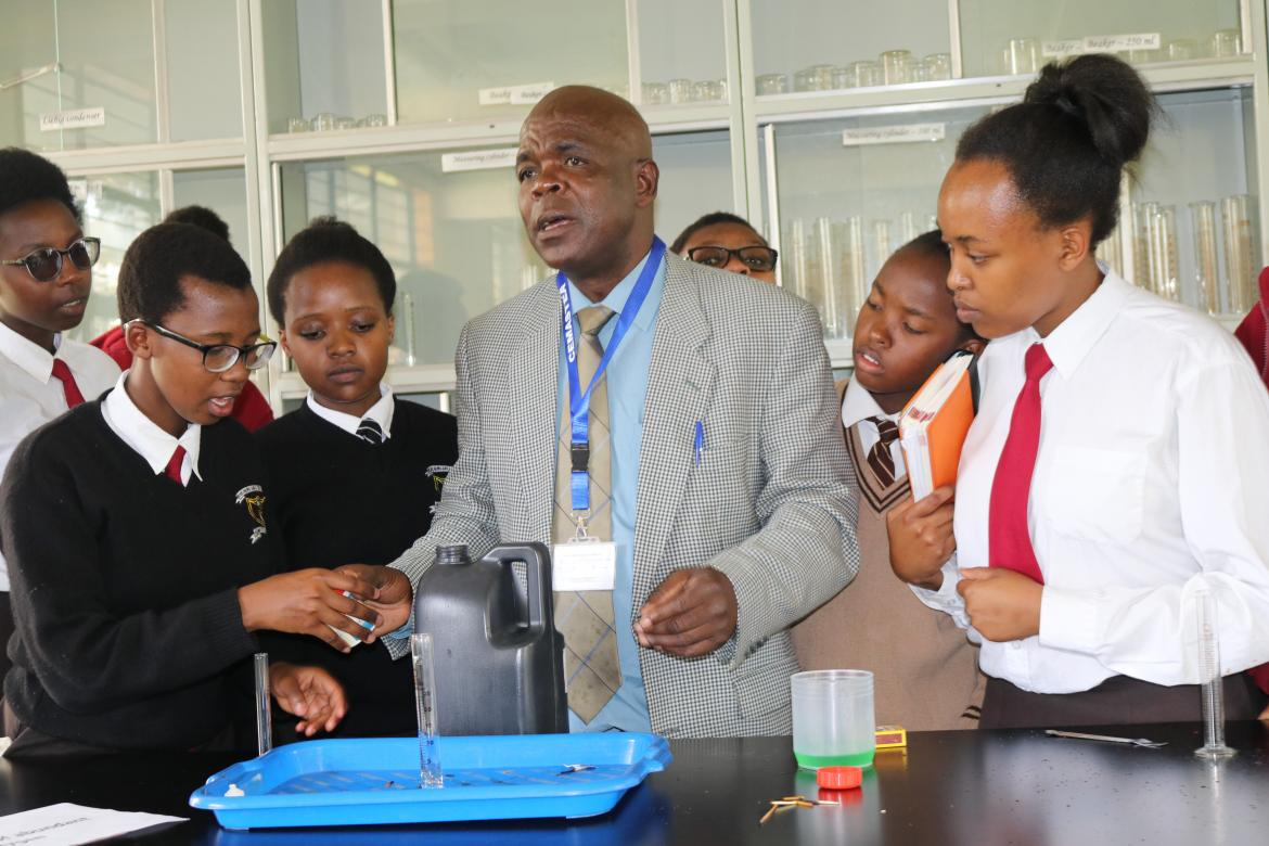 Richard Jakomanyo a trainer at CEMASTEA explains to students through an innovative way of illustrating a chemistry concept – Copyright: CEMASTEA, 2018