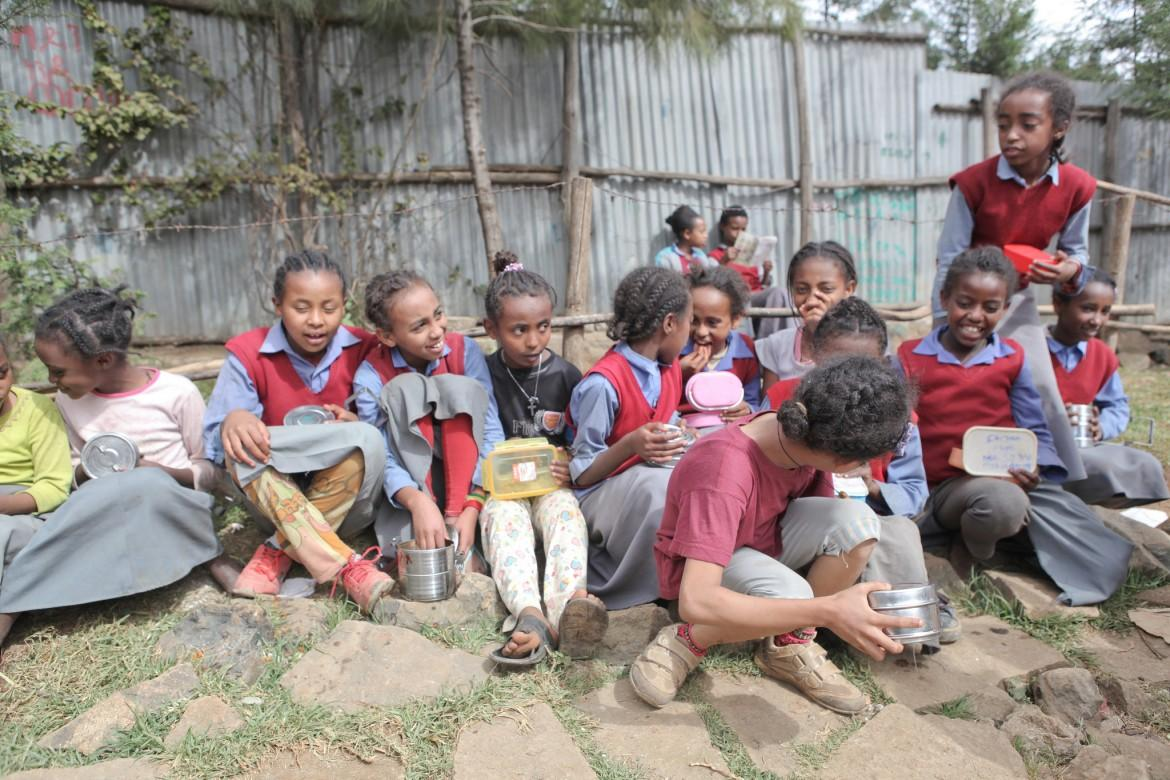 School girls sit outside on the school grounds to have lunch at a school in Ethiopia. CREDIT: GPE/Midastouch