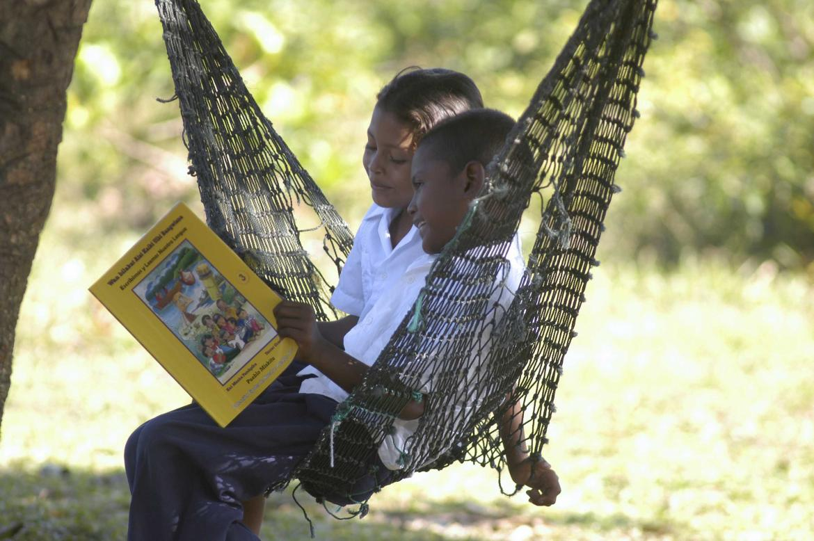 Two children read a book in a hammock. Honduras. Credit: GPE/Paul Martinez
