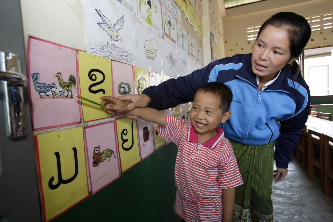 A teacher in Laos helps a student with the answer to a problem at the front of the class, (c) Plan/Jim Holmes