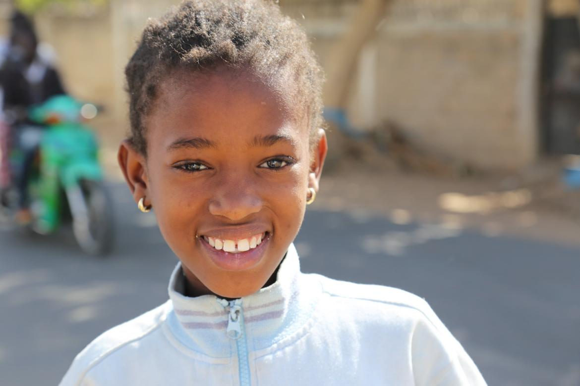 A girl smiles in front of her school in Tivaouane, Senegal. Credit: GPE/Chantal Rigaud