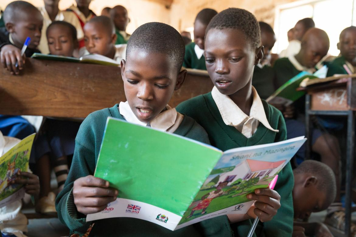Students read a supplementary reading book during class. Kivukoni Primary School, Mpanda MC, Katavi, Tanzania.