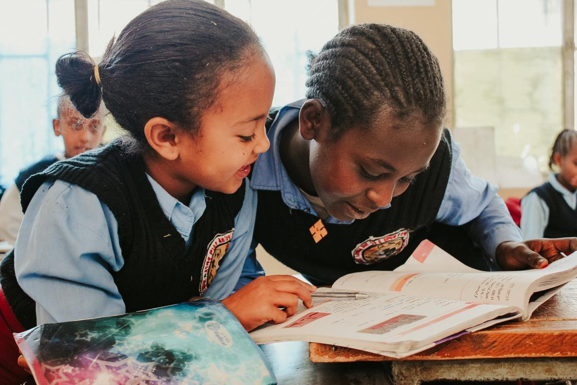 Makbel Henok (left) and her classmate sharing a textbook in class. Makbel is 7 years old and is in grade 2.